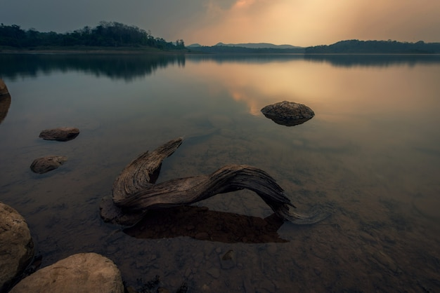 Landscape of a sunset over the water of the lake with timber- image