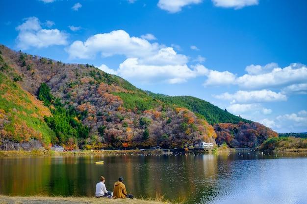 河口湖の紅葉と日本の川沿いに座っているカップルの風景を見る
