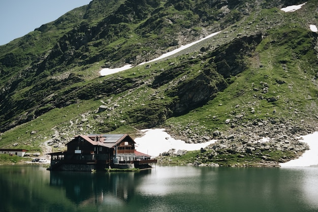 Landscape view of balea lake in romania and fagaras mountains in the summer with snowy peaks