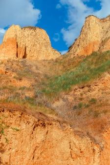 풍경 보기 클레이 곶 절벽 푸른 하늘을 배경으로 찰흙 산의 경사면에서 자란 푸른 잔디 잔디...