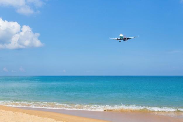 飛行機が滑走路に着陸する間、青い空と海の金色の砂が含まれている風景の景色