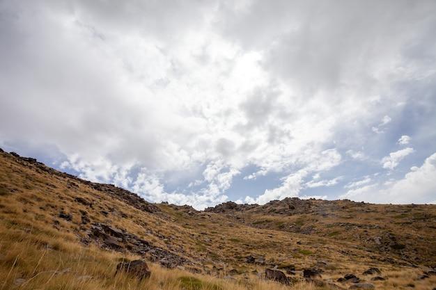 Vista del paesaggio di una collina secca sotto un cielo nuvoloso in sierra nevada, spagna