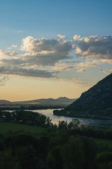 Vista del paesaggio delle colline sulla riva di un lago calmo sotto il cielo blu