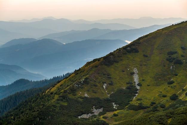 夜明けの光の霧で覆われた緑の雄大なカルパティア山脈の景観。