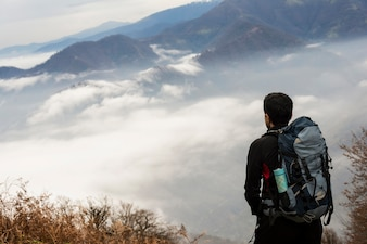 Landscape view of hazy autumn mountain hills and hiker with backpack in foreground