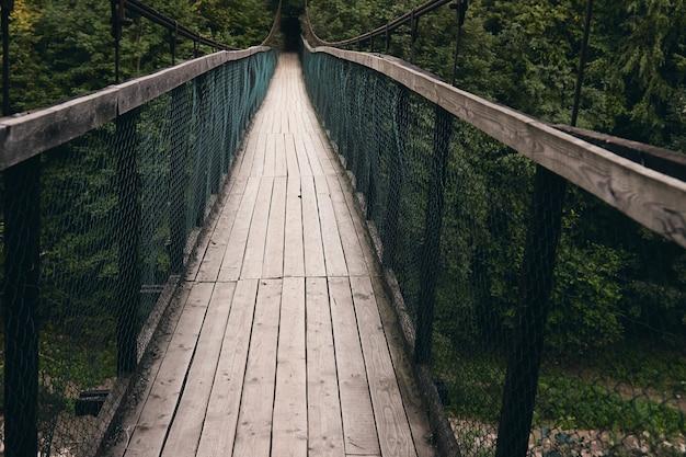 Ландшафтный вид на длинный стальной подвесной мост. старый небольшой деревянный мост через реку только для пешеходов. горная река в окружении гор и альпийского леса.