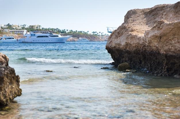 빈 해변에 있는 바위와 돌의 풍경, 배경의 바다에 있는 요트
