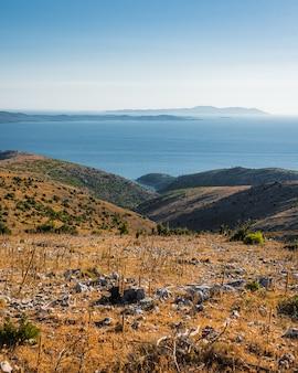 青い空の下の穏やかな湖の岸にある丘の風景ビュー