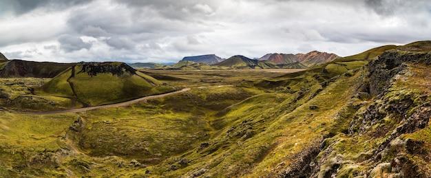 青空の下でアイスランドのハイランド地方の山々と野原の風景