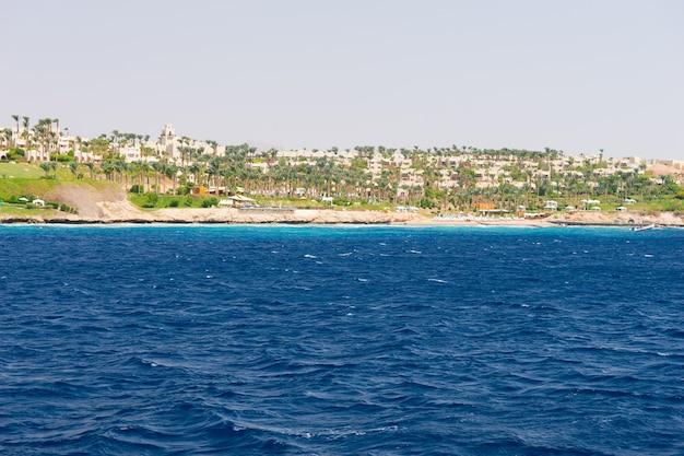 바다의 풍경, 호텔, 야자수 및 기타 식물이 배경으로 있는 해안선