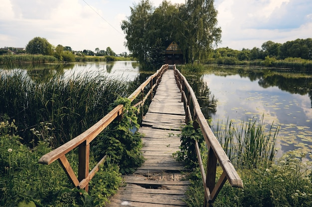 Landscape view of old small wooden bridge across the lake. fishman house on an island surrounded by wather and forest.