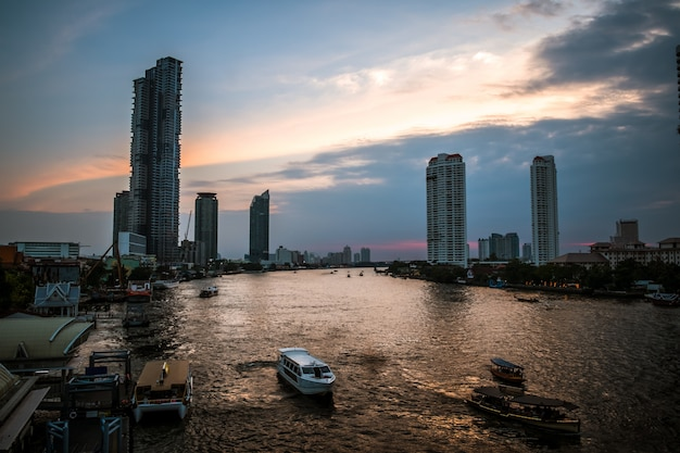 Landscape view of sunset at chaophraya river with a view of boats and modern building along the riverside.