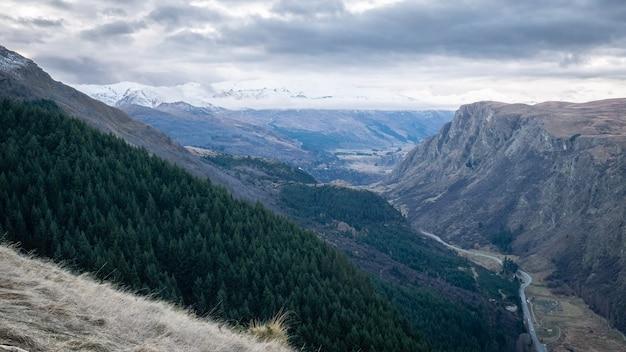 風景は劇的な空のクイーンズタウンニュージーランドと谷と山を表示します
