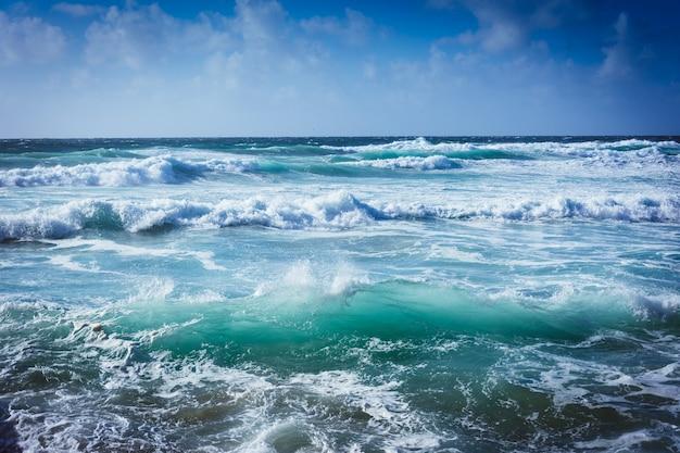 Paesaggio di un mare ondoso sotto la luce del sole e un cielo blu