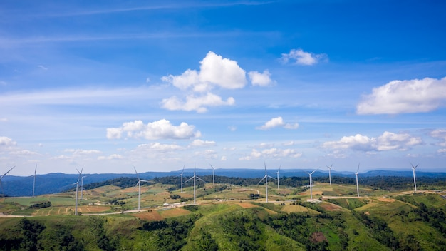 Пейзаж ветровых турбин на горных угодьях и фоне голубого неба