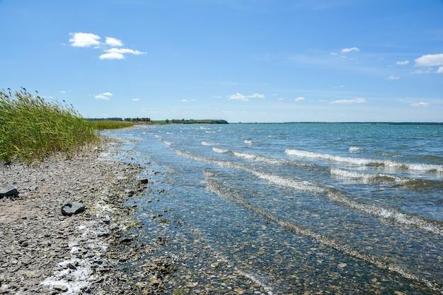 Пейзаж с чистым озером и голубым небом с облаками