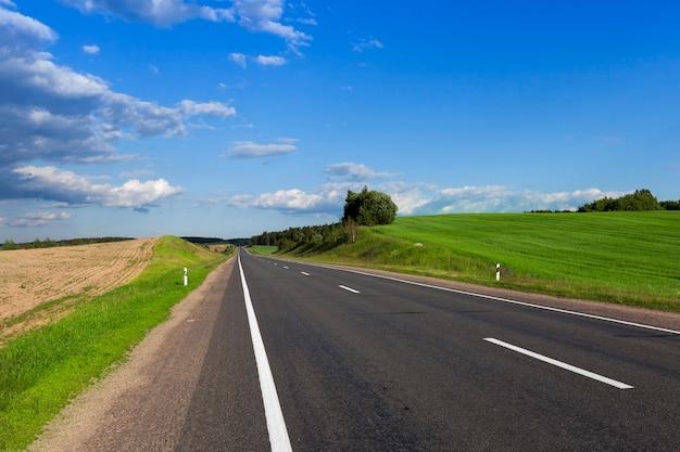 봄 시즌에 아스팔트 고속 도로가있는 풍경. 도로 가장자리에는 푸른 잔디, 식물 및 나무가 자라는 언덕이 있습니다. 푸른 하늘과 흐린 날씨