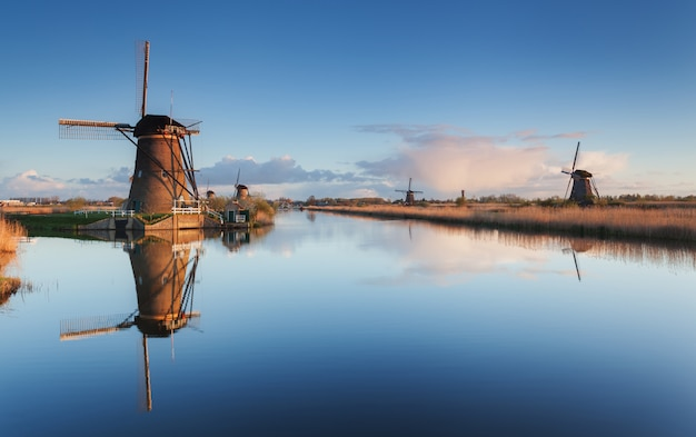 日の出の美しい伝統的なオランダ風車のある風景
