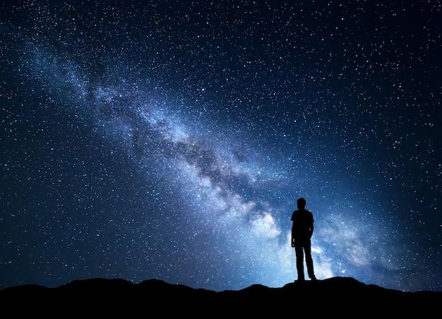 푸른 은하수 풍경. 별과 산에 행복 한 남자의 실루엣 밤 하늘.