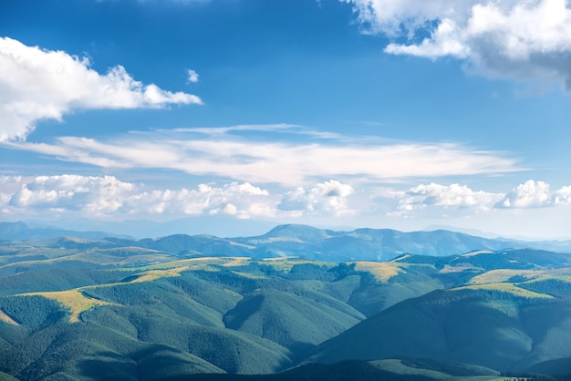 Landscape with blue mountains, forest and white clouds on sky