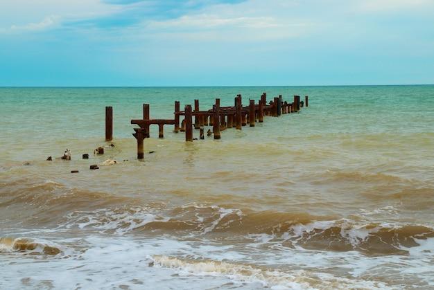 Пейзаж со сломанным причалом и бурным морем