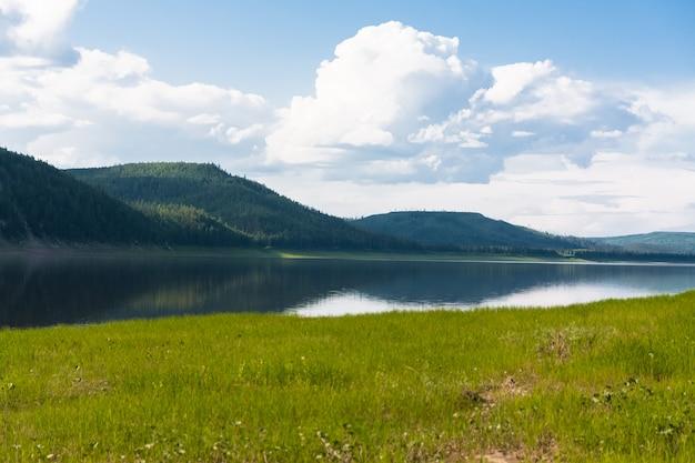 Пейзаж с облаками над водой. река тунгуска. красноярский край.