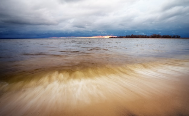 Landscape with cloudy sky and a lake with waves. composition of nature