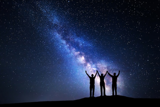 Landscape with colorful milky way and silhouette of a happy family with raised-up arms on the mountain. night starry sky. beautiful universe.