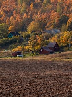 秋の背景に丘の上の村があり、植栽の準備ができている農地のある風景。垂直方向のビュー。