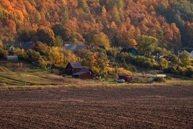 秋の背景に丘の上の村があり、植栽の準備ができている農地のある風景。