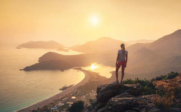 女の子、海、山の尾根、オレンジ色の空のある風景