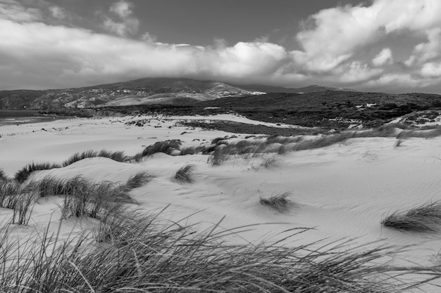 A landscape with grass covered with sand surrounded by mountains under the storm clouds