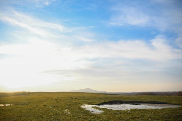 緑の草原と夕焼けの雲と青い空のある風景します。