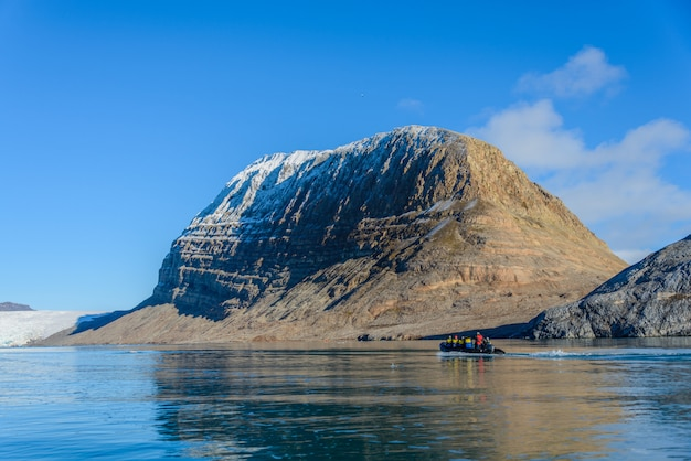 Landscape with iceberg in greenland at summer time. sunny weather. inflatable boat with tourists.