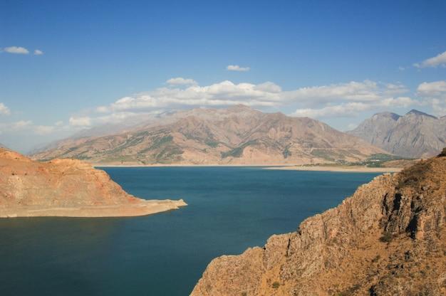 湖と山の景色を望む風景。ウズベキスタン、チャルヴァク貯水池。中央アジアの性質