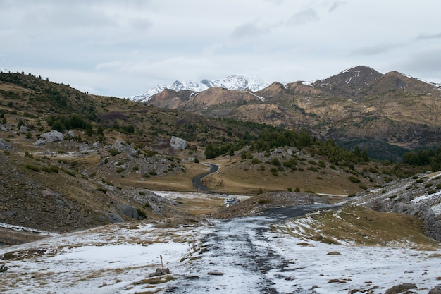 Landscape with a lot of rocky mountains covered with snow under a cloudy sky