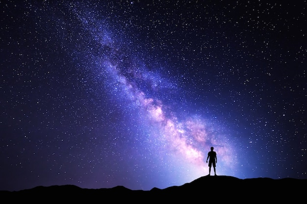 Landscape with milky way. night sky with stars and silhouette of a standing happy man on the mountain.