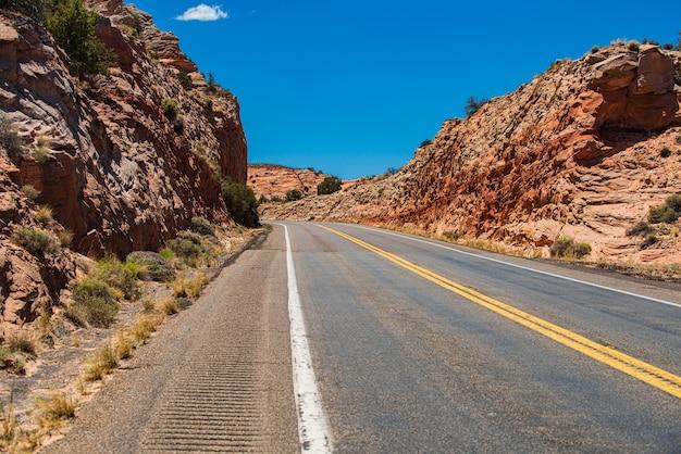Landscape with orange rocks, sky with clouds and asphalt road in summer.