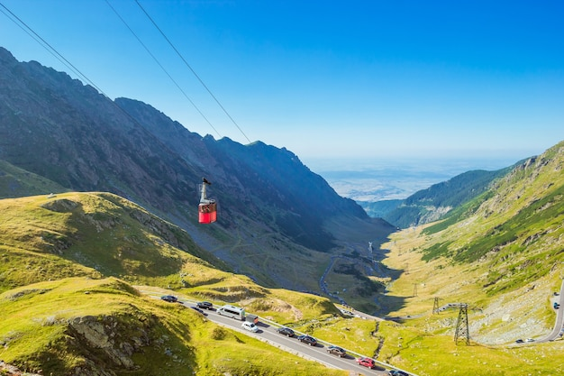 Landscape with red cable car above the transfagarasan alpine road in carpathian mountains in sunny day. .