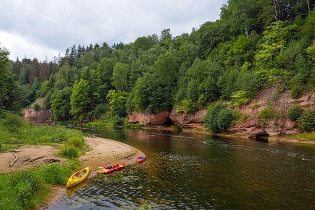Gauja 강둑의 사암 절벽, 카누 및 카약, 빠르게 흐르는 맑은 강물, kuku 절벽, gauja 국립 공원, 라트비아 풍경