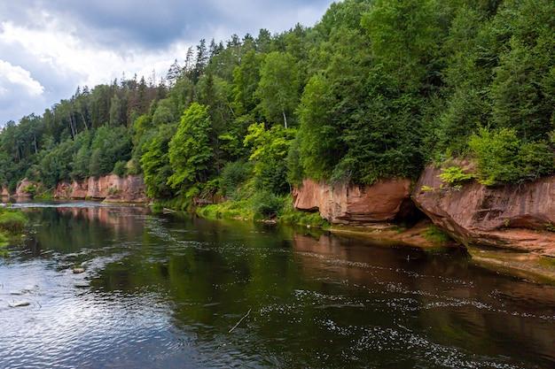 ガウヤ川の土手に砂岩の崖、流れの速い澄んだ川の水、ククの崖、ガウヤ国立公園、ラトビアのある風景