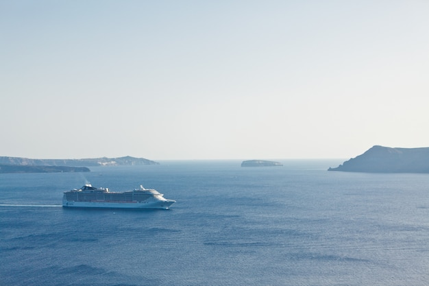 A landscape with sea view. cruise liner at the sea near the island santorini, greece