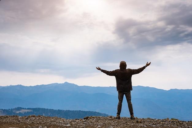 曇り空を背景に山頂に立っている幸せな男のシルエットと腕を上げた風景。山の秋の雨