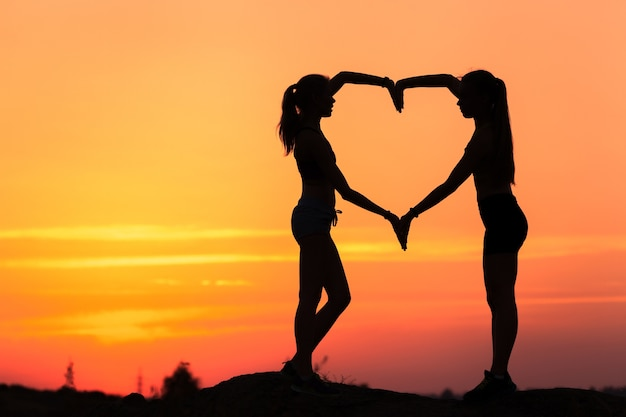 Landscape with silhouette of young sporty women holding hands in heart shape on the background of colorful sky at sunset in summer time.
