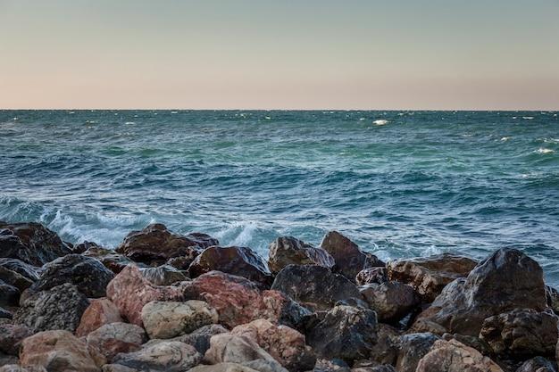 Landscape with stone coast, sea and blue sky