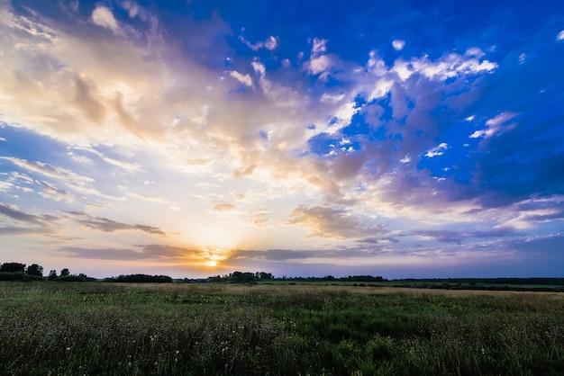 Пейзаж с восходом и солнцем на пасмурном голубом небе над полем летом