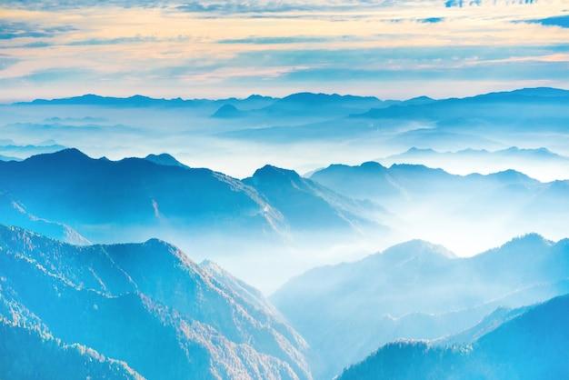 Пейзаж с закатом в синих горах и тумане