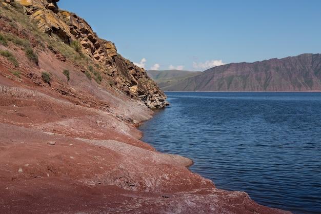 Пейзаж с морскими скалами на берегу и горами