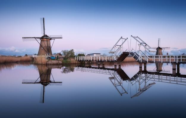 伝統的なオランダ風車のある風景と日の出の跳ね橋