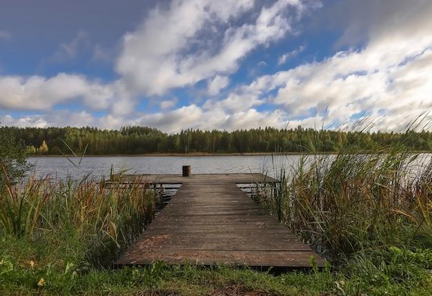Пейзаж с длинной деревянной пристанью со стулом для рыбалки, озерный лес на горизонте и пасмурное голубое небо ...